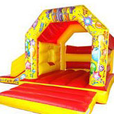 A bouncy castle with a slide on the left side. Red and yellow with a party theme.